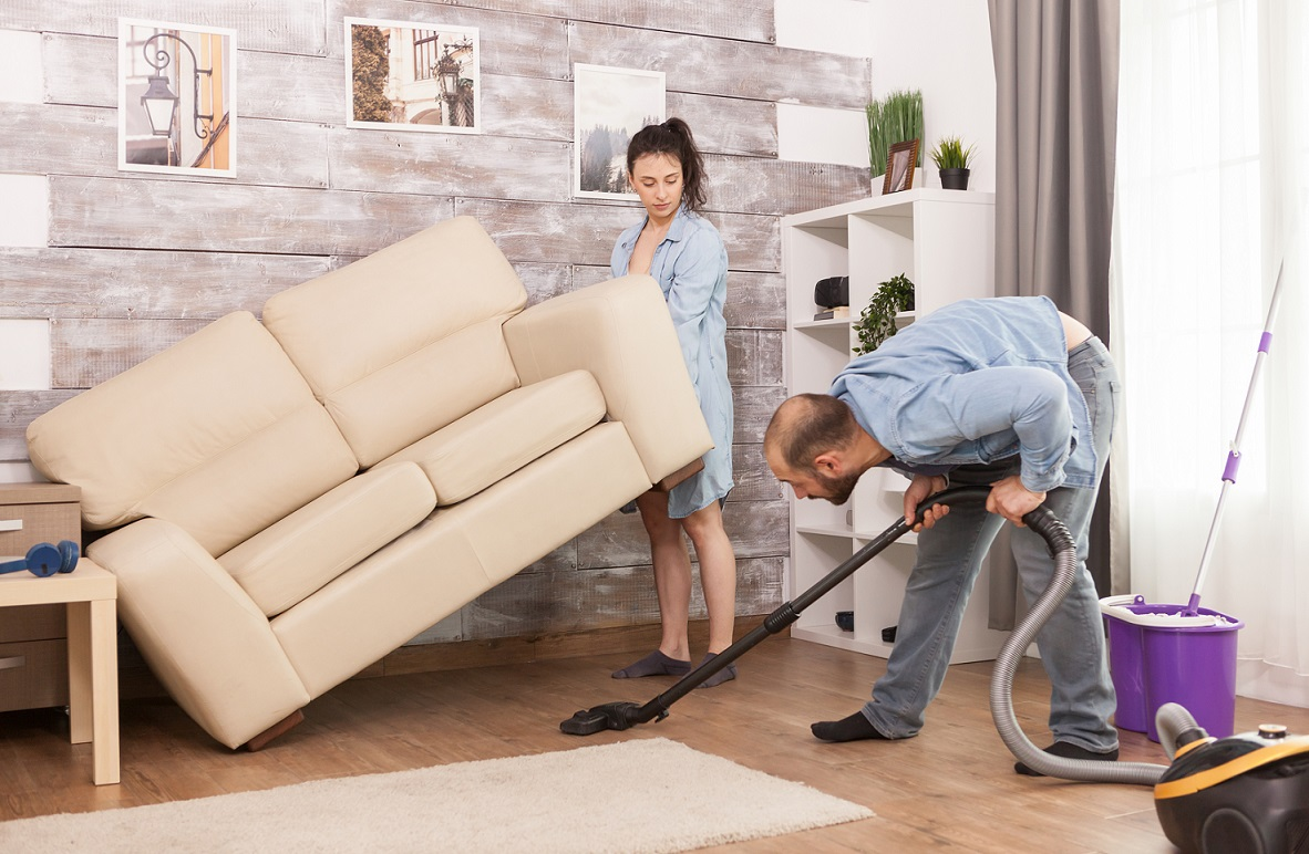 Wife picks up sofa for husband to clean dust under it with vacuum cleaner.