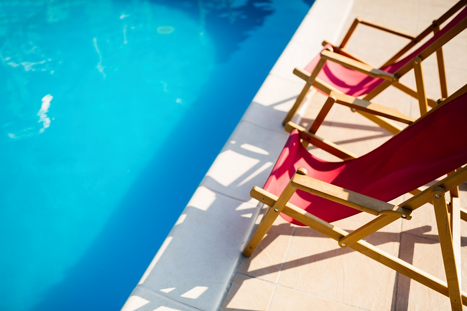 Deck chairs at side of pool symbolizing summer vacation