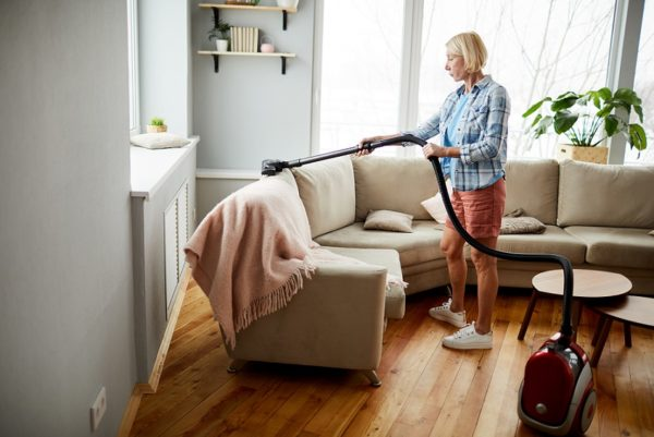 Serious attractive mature woman in homewear using vacuum cleaner while cleaning upholstery on sofa in living room