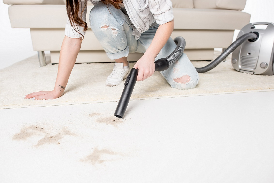 Low section view of woman removing floor stains with vacuum cleaner isolated on white
